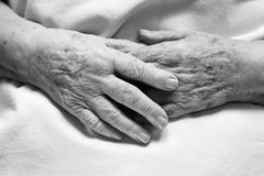 Hands of an old person. In bed royalty free stock image