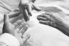 Hands of an old person. In bed Stock Image