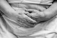 Hands of an old person. In bed stock photo