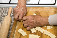 Hands of old woman by the cooking Royalty Free Stock Images