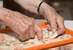 Hands of old woman at cooking Stock Photos