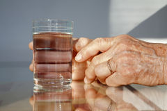 Hands of old woman and glass of water Royalty Free Stock Photo