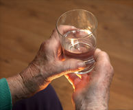 Hands of old woman and glass of water Stock Image
