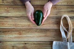 Hands of an old woman holding fresh organic avocado. Eco Shopping Bag on wooden background, Flat Lay royalty free stock image