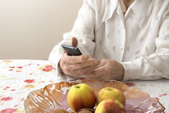 Hands of an old woman holding a mobile phone. Grandmother sitting at a table in the living room and holds in his hands the phone Royalty Free Stock Photos