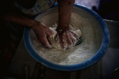 Hands of an old woman knead the dough in a bowl royalty free stock images