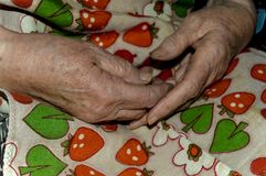 Hands of an old woman. Kneeling close-up Stock Photo