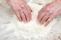 Old hands in flour. Hands of the old woman make a hole in the flour scattered on the table Stock Photos