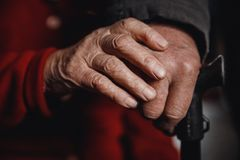 Hands of an old woman and man holding cane, skin wrinkled royalty free stock photos