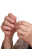 Hands of the old woman pass  thread in  needle Royalty Free Stock Image