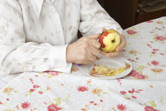 Hands of the old woman peeling an apple. The old woman sits at a table in the living room Royalty Free Stock Photography