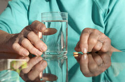 Hands of old woman with a pill and water Stock Photos