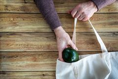 Hands of an old woman put fresh organic avocado in Eco Shopping Bag on wooden background, Flat Lay stock photo