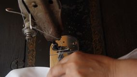 Hands of an old woman scribbling white cloth on an old manual sewing machine. Double edge fabric edge processing. stock footage