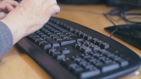 Hands of old woman typing on a computer keyboard. Close up hands of old woman typing on a computer keyboard, 4K stock footage