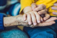 Hands of an old woman and a young man. Caring for the elderly. c stock photos