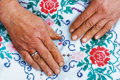 Hands of old women. Lying on linen of fabric Royalty Free Stock Image