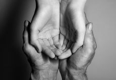 Hands of the old and the young man. Black and white. top view Stock Photography