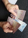 Hands of an older man counting brazilian banknotes. Insurance with retirement and protection plan, investment for monthly pensions to adulthood, need of economic stock images