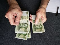 Hands of an older man counting chinese banknotes. Insurance with retirement and protection plan, investment for monthly pensions to adulthood, need of economic royalty free stock photography