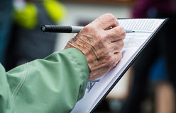 Hands of an older woman drawing on a sketch pad at the farmers market. Stock Photography