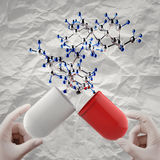 Hands open capsule show molecule on crumpled paper background Stock Images