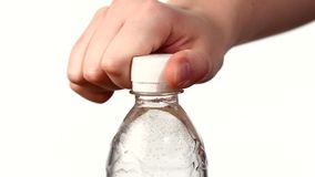 Hands opening a bottle of fresh water on white. Background, slow motion, cam moves upwards stock footage