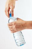 Hands opening a bottle of mineral water Stock Image