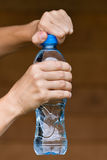 Hands opening bottle with water Stock Photography