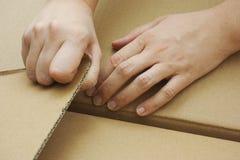 Hands opening cardboard box stock image