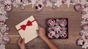 Hands opening christmas present inside seasonal decorations frame stock footage