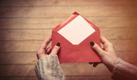 Hands opening envelope. Beautiful woman hands opening big red envelope on the wonderful brown wooden background Stock Photos
