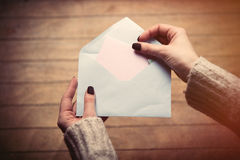 Hands opening envelope. Beautiful woman hands opening big white envelope on the wonderful brown wooden background Stock Photography