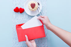 Hands opening red romantic envelope. Against of decorated table with cupcake and two hearts.From above Stock Images