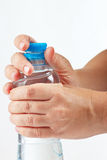 Hands opening a small bottle of mineral water Royalty Free Stock Photos