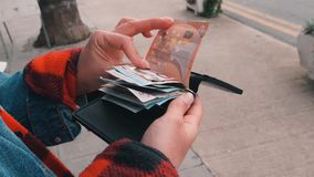 Hands opening wallet cash holder and counting euros. Woman opens cash holder wallet and counts cash euro bills. Hands opening wallet cash holder and counting stock footage