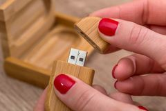 Hands opening wood USB Flash. Drive stock photography