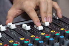 Hands operating sound console. Male Hands operating small Sound console on the table Royalty Free Stock Photo