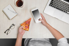 Hands ordering pizza with a device over a wooden workspace table.  Stock Image
