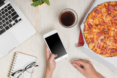 Hands ordering pizza with a device over a wooden workspace table.  Stock Images
