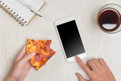Hands ordering pizza with a device over a wooden workspace table.  Royalty Free Stock Image
