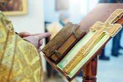 The hands of an Orthodox priest, a cross and a prayer book. stock photos