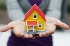 Hands outstretched holding a house Stock Photography
