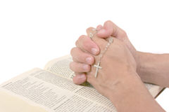 Hands over Bible praying. Isolated on white Stock Image