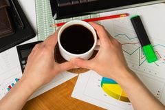 Hands over financial chart background. Businesswoman hands with cup of coffee over paper and financial chart background Royalty Free Stock Photos