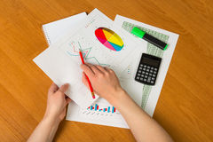 Hands over financial chart background. Businesswoman hands over paper and financial chart background Stock Photography