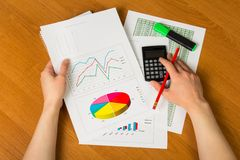 Hands over financial chart background. Businesswoman hands over paper and financial chart background Stock Image