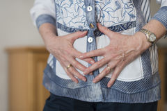 Hands over his stomach Royalty Free Stock Photography