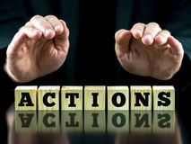Hands Over Letter Tiles Spelling the Word Actions Royalty Free Stock Photography