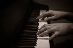 Hands over a piano keyboard Stock Images